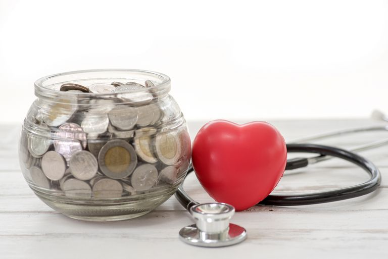close up stack of coins and hand holding red heart background