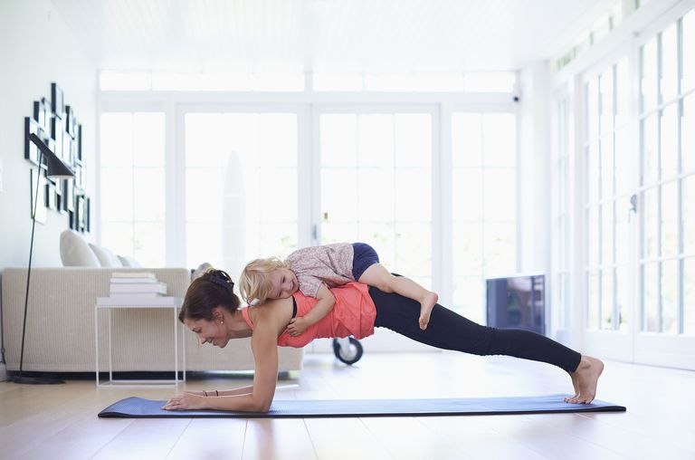 toddler lying on mother's back while she does yoga