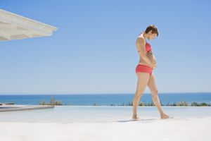 Pregnant woman at poolside holding stomach