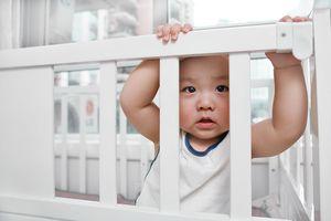 Baby boy looking through his crib