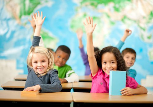 first grade class students raising hands smiling
