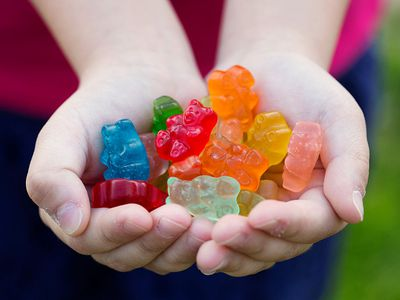 A child holding gummy candy.