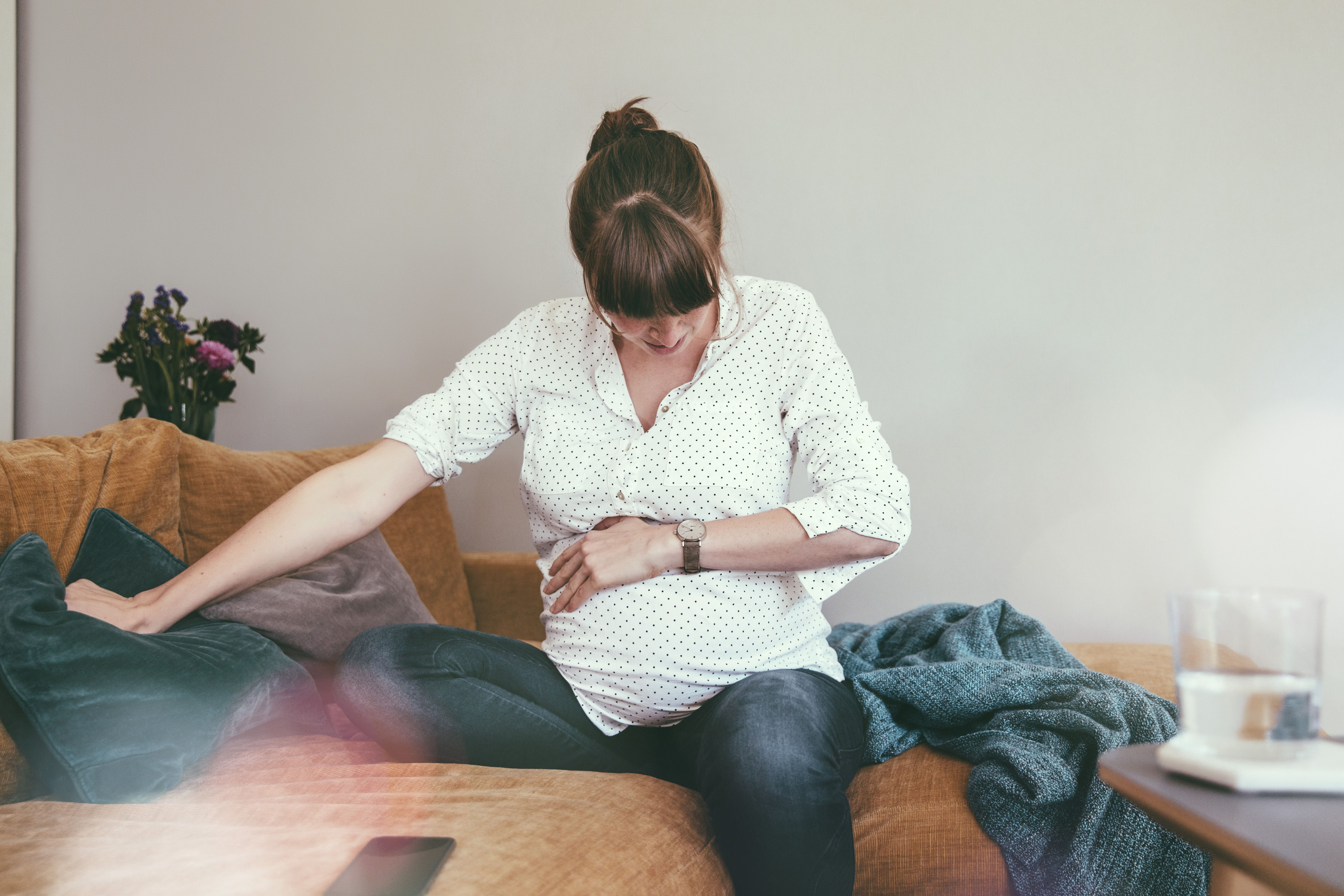 Expectant mother timing her contractions while sitting on couch at home