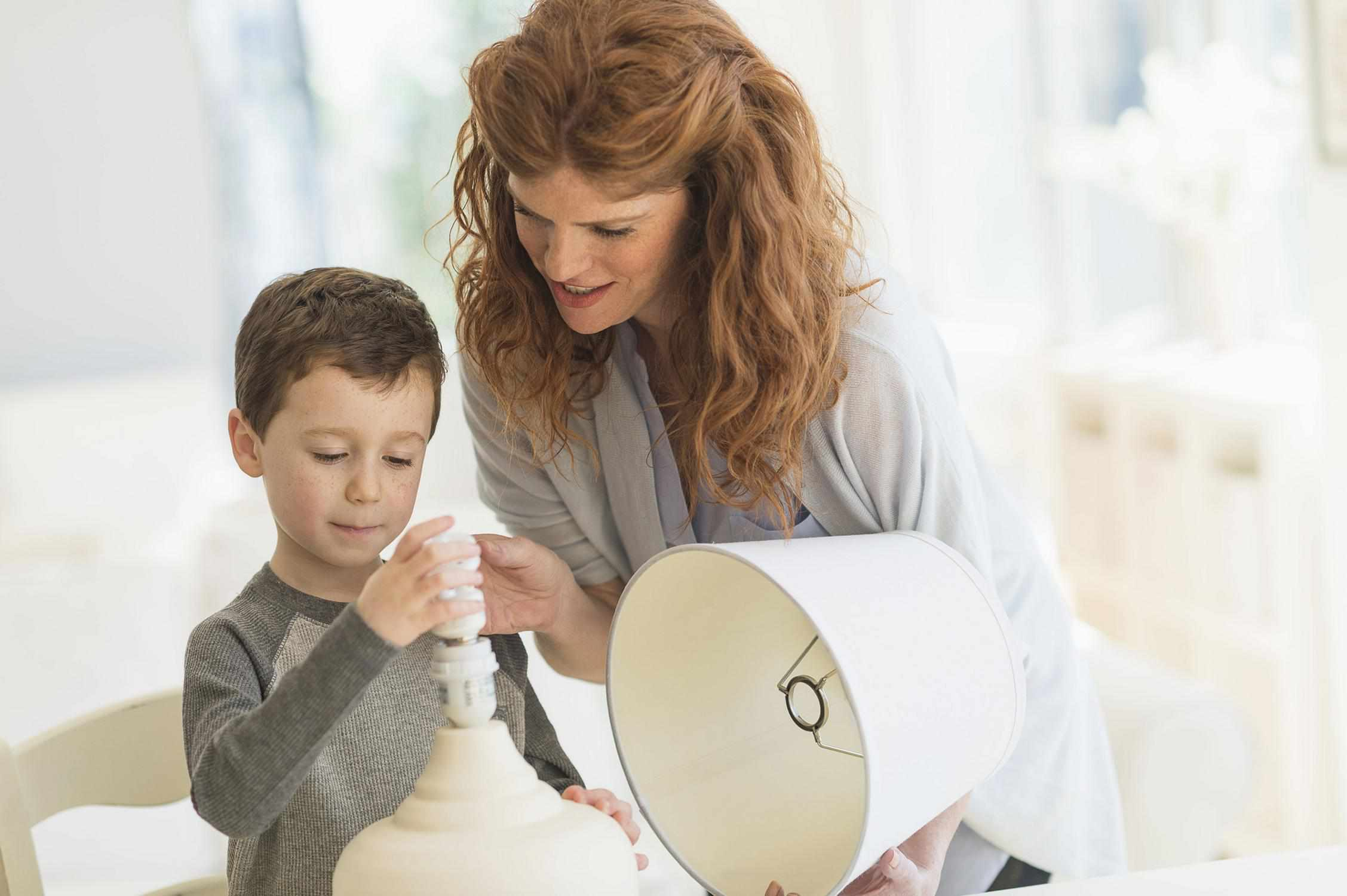 mom showing her son how to change a light bulb