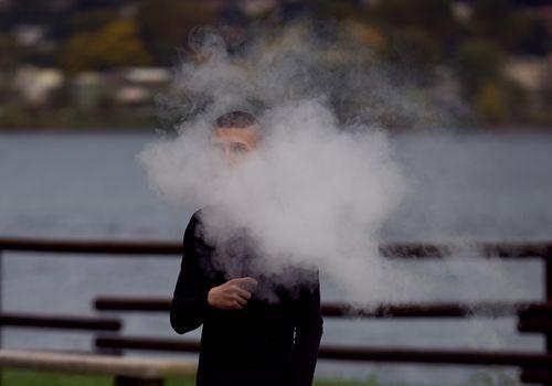Teenager in a cloud of vape smoke