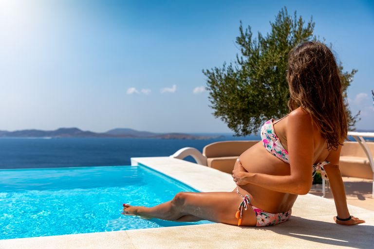 pregnant woman sitting by a pool