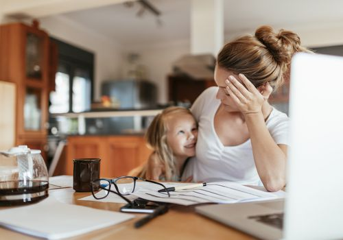 Frustrated mother hugging her child when interrupted while working at home