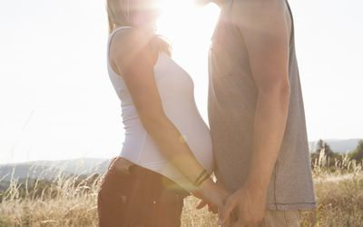Young man and pregnant girlfriend face to face and holding hands in field, waiting to meet their baby on the due date