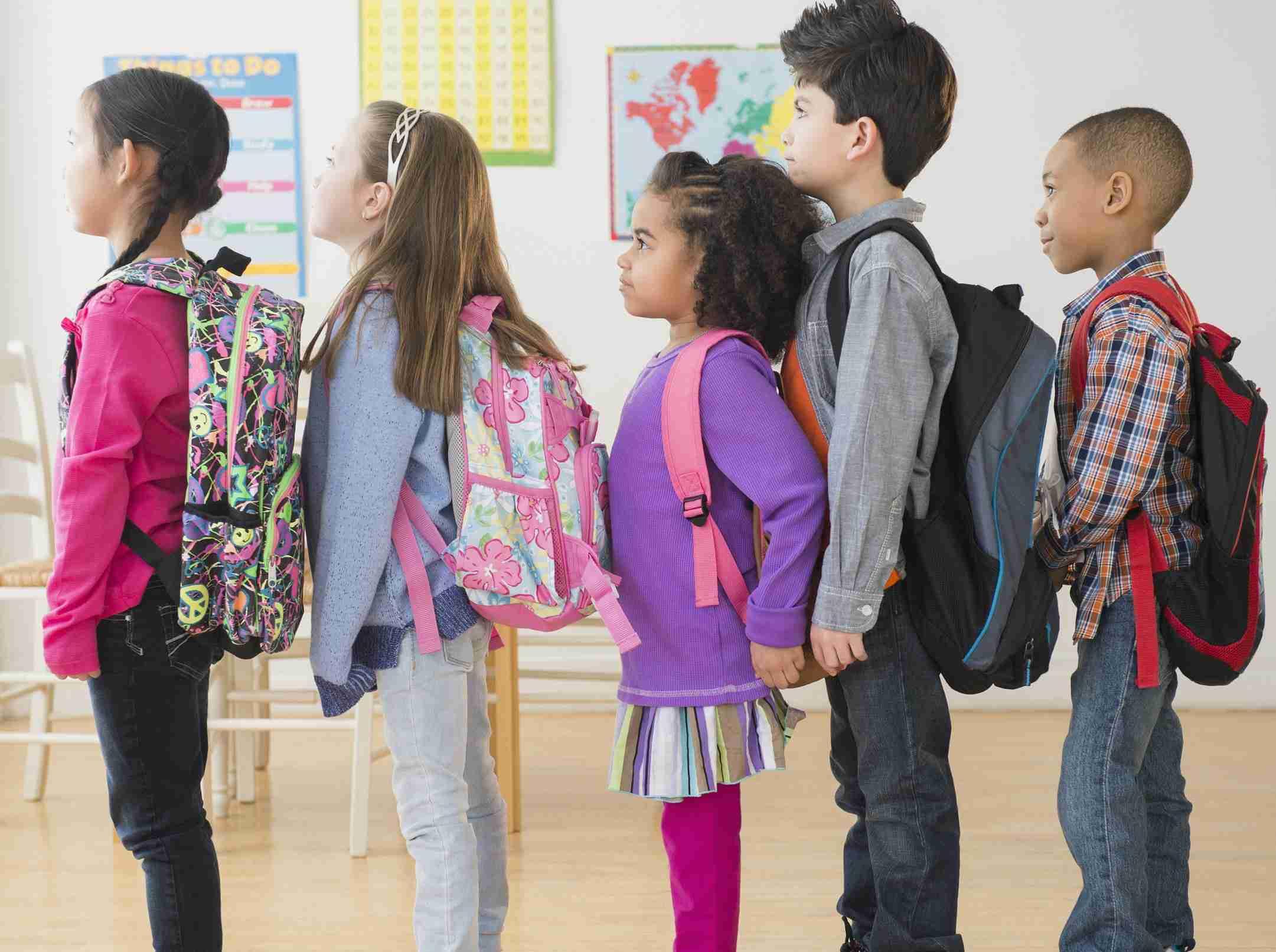 Kinder in der Klasse mit Schulrucksäcken