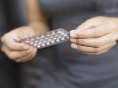Woman holding blister pack of birth control pills