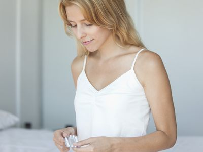 woman sitting on bed holding a container with birth control pills