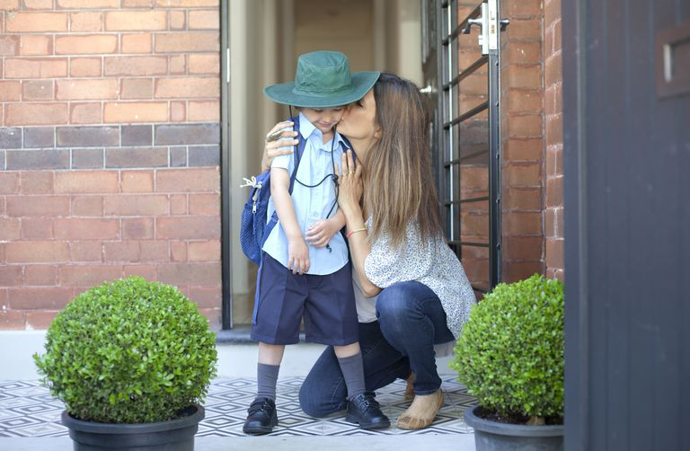 Mother kissing child in school uniform.