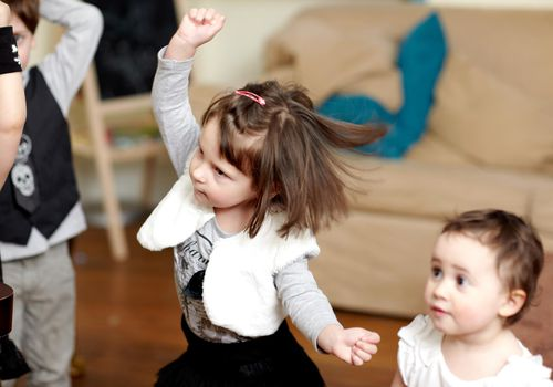 Toddler girl dancing in living room with other kids