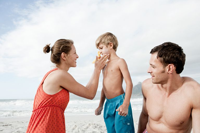 Mother applying sunscreen to child's face