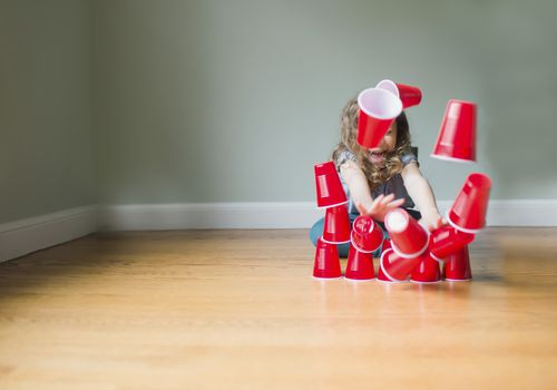 Playful girl breaking pyramid made of disposable cups while sitting on floor at home
