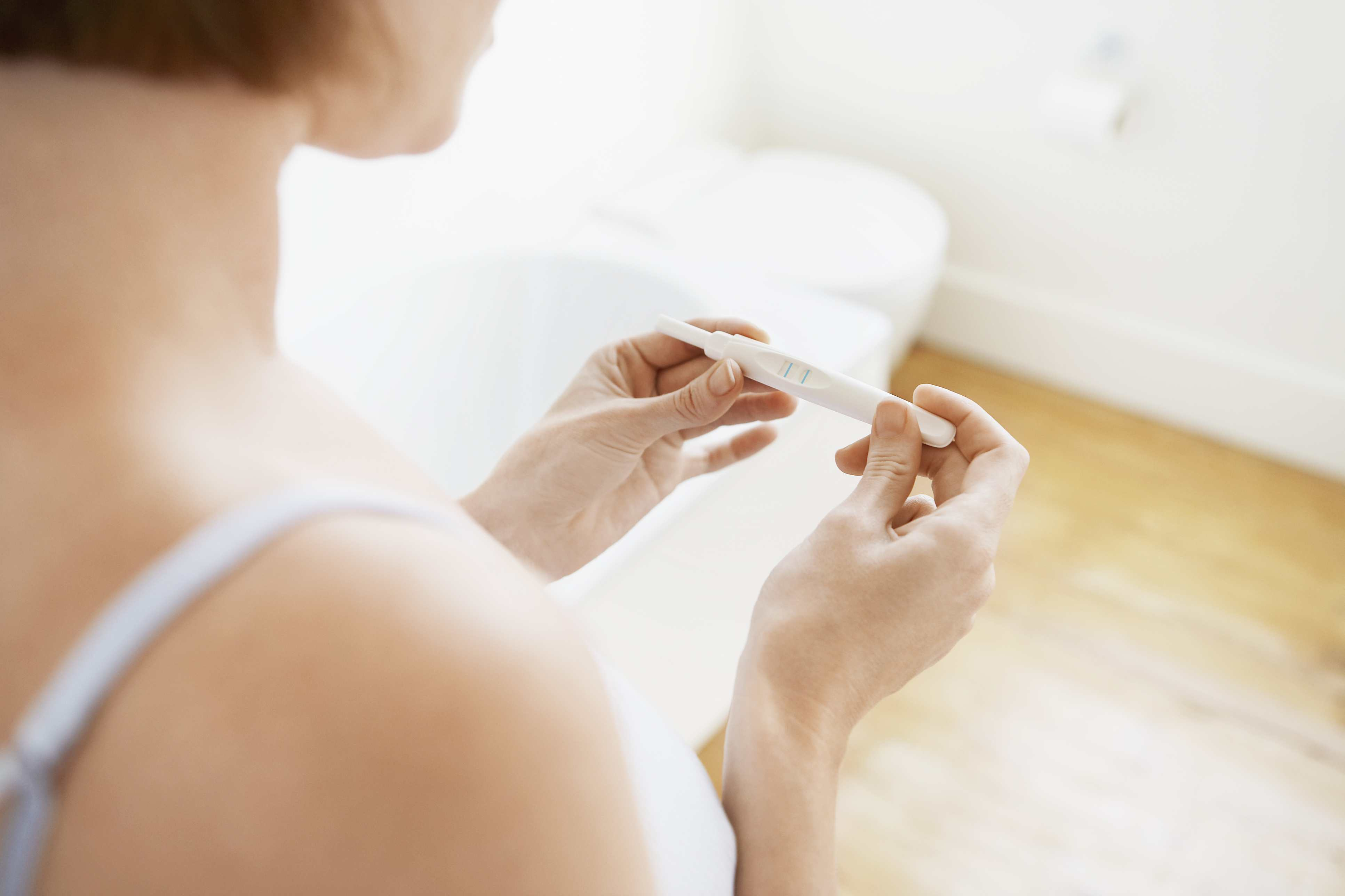 woman holding a pregnancy test