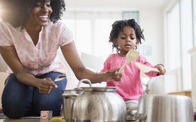 Mother and daughter playing with pots and pans