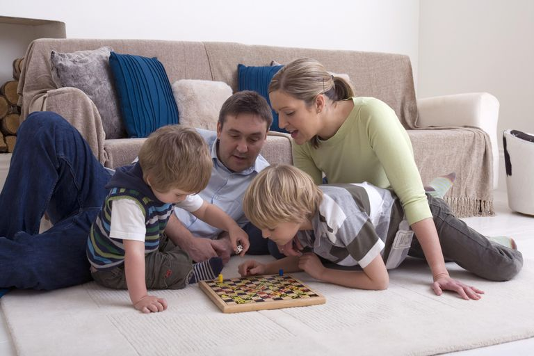 Man and woman playing board game with two boys, sitting on a rug on the living room floor