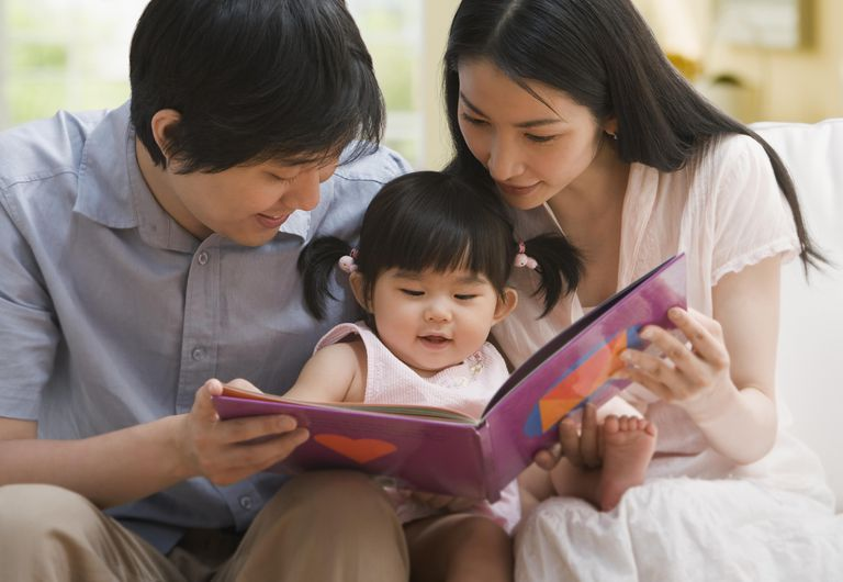 Parents read to their young child.