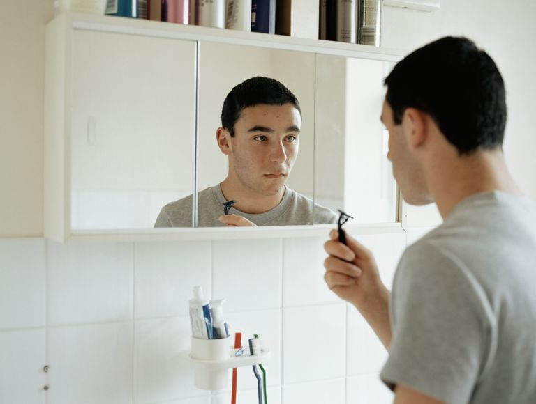 Teen boy shaving in a bathroom mirror