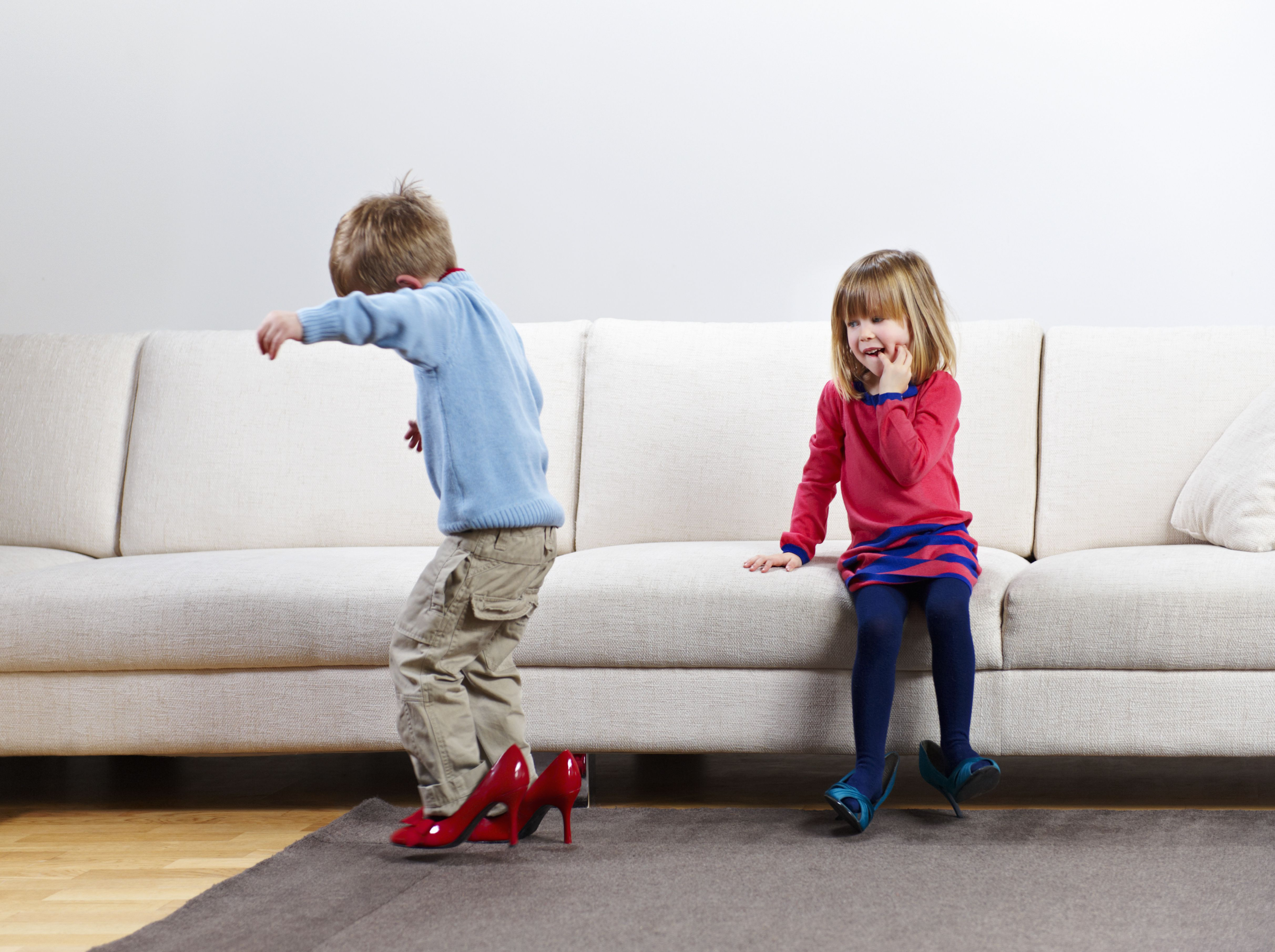Young boy and girl walking in high-heels