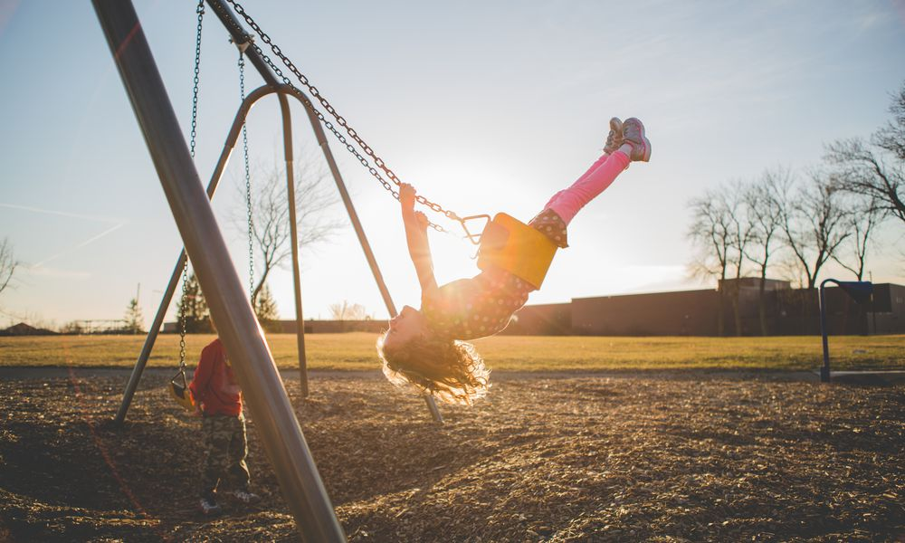 Girl swinging gleefully on a swingset.