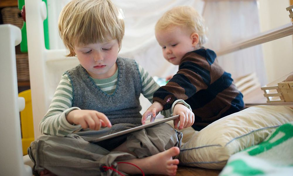 Boy (4-5) and Girl (1) play with iPad and iPhone