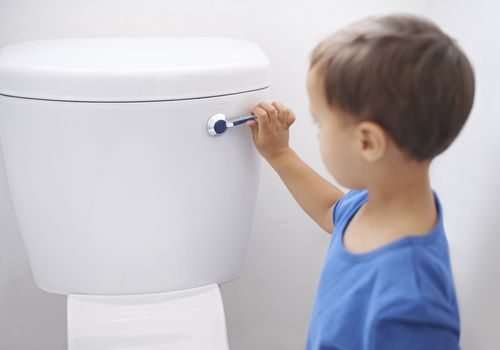 A young boy flushing a toilet