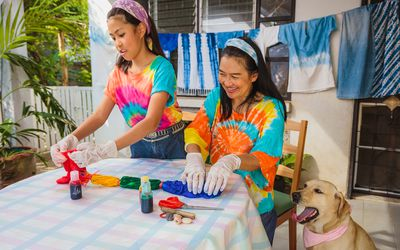 Woman and child do tie-dye at a table outside. There are tie-dye pieces drying behind them and a dog next to the table.