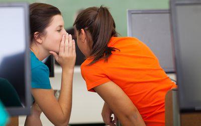 two girls gossiping in class