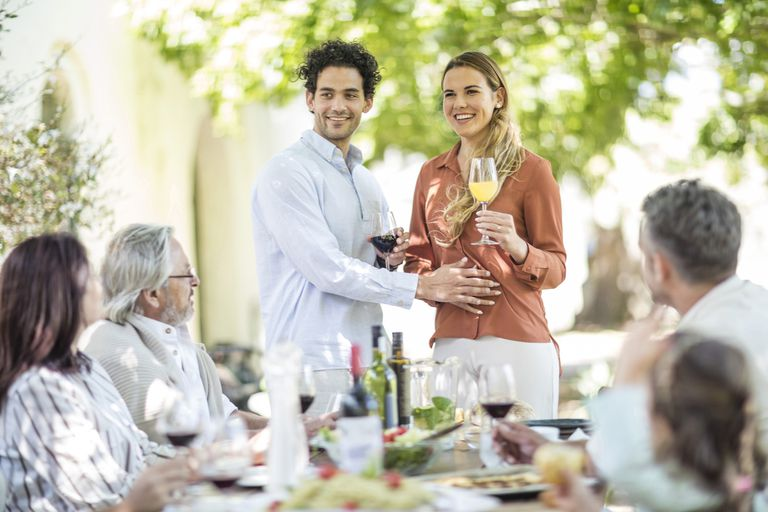 Young couple raising a toast with announcement of pregnancy to family during outside family lunch