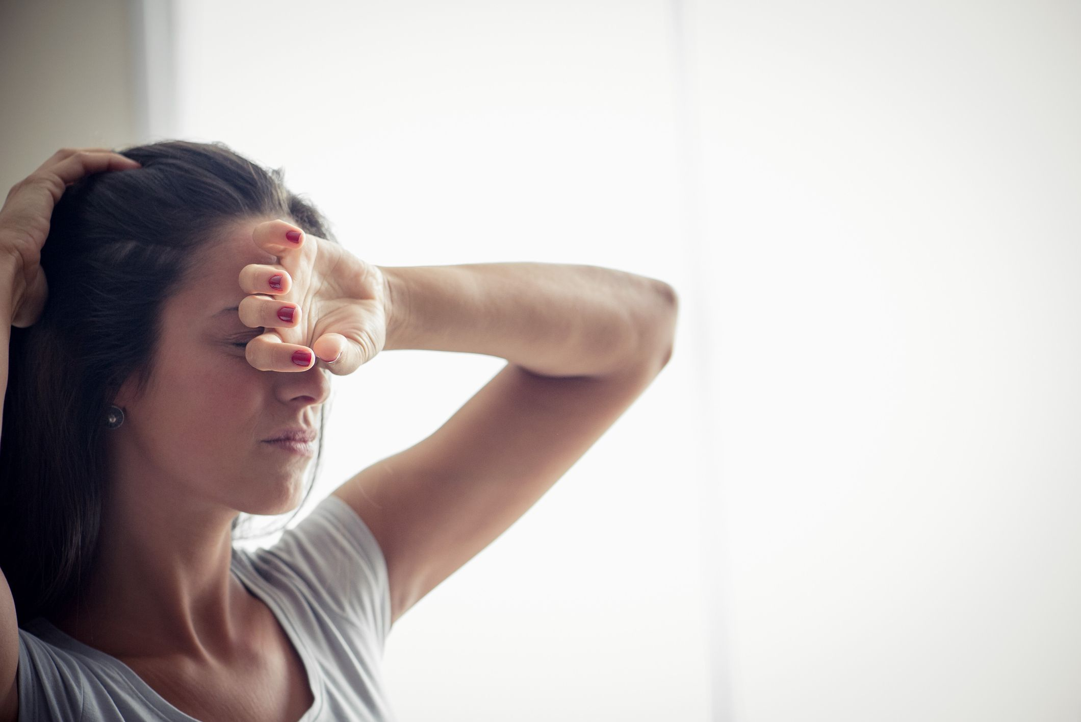 Woman in pain putting her arm up to her head