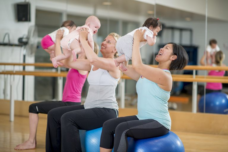 Women holding babies on exercise balls in an exercise class.