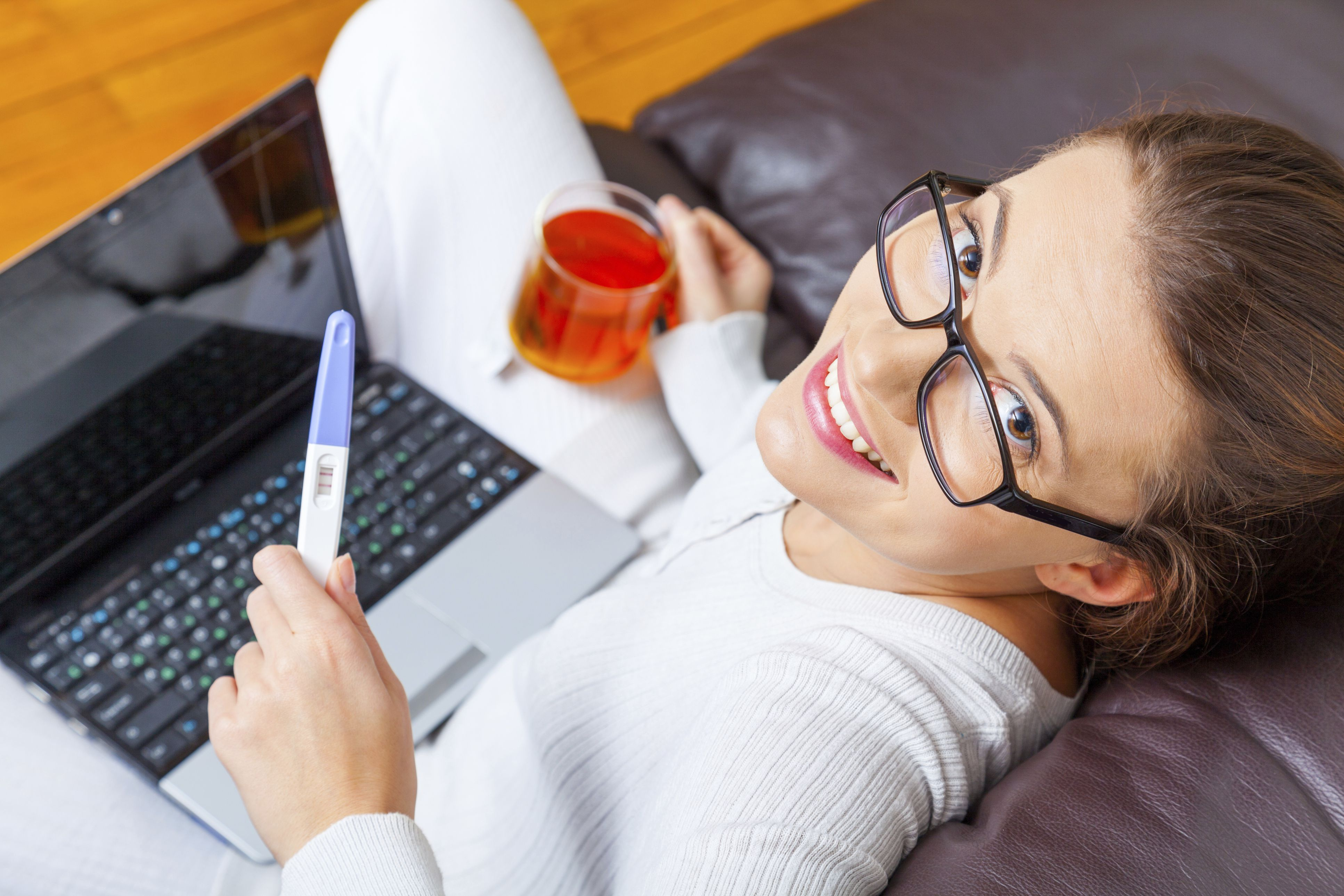Woman holding positive pregnancy test result and cup of tea