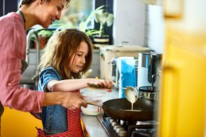 Girl pouring pancake batter in frying pan, with mother