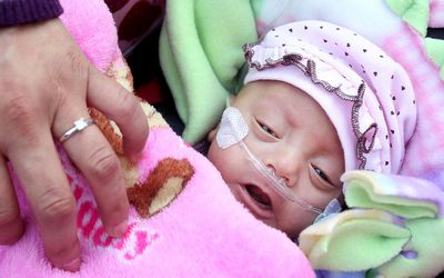 Haydee Ibarra, 22, covers her daughter Melinda Star Guido with her blanket as they leave the Los Angeles County-USC Medical Center January 20, 2012 in Los Angeles, California. Melinda Star Guido, the third smallest surviving baby known in the world, was born on August 30, 2011 weighing only 9.5 ounces.
