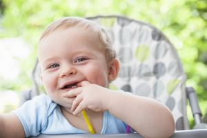 Portrait of baby boy with fingers in mouth on high chair in garden