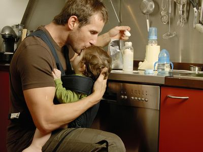Father carrying baby son (7-9 months) while preparing milk in kitchen