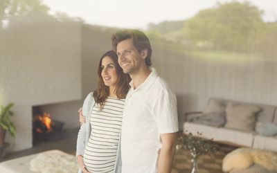Smiling pregnant couple looking out living room window
