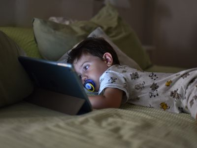 Tired child on a bed looking at a tablet
