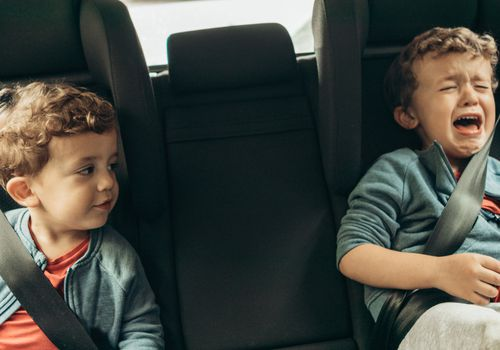 Twins in the car, one is crying