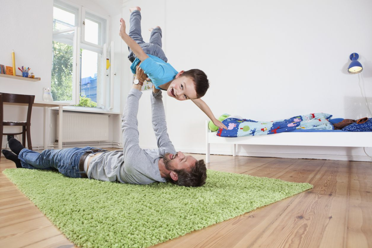 father playing with son in bedroom