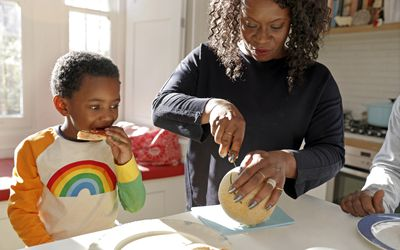Mother cutting cantaloupe for kids