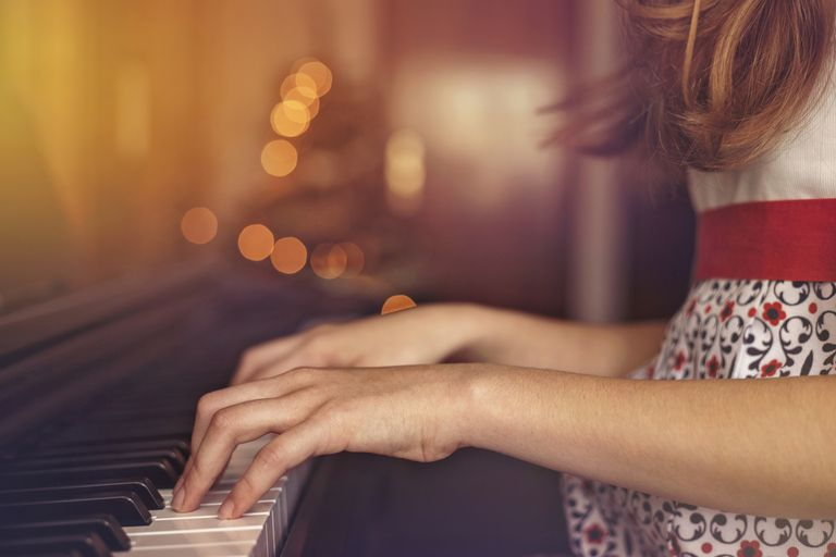 Close up of the hands of a girl playing the piano.