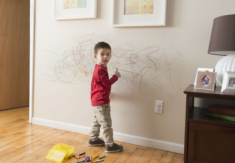 Young child drawing on wall