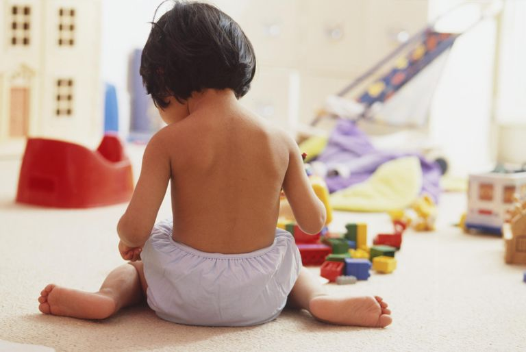 Rear view of a dark-haired girl toddler wearing trainer pants sitting on floor, surrounded by toys