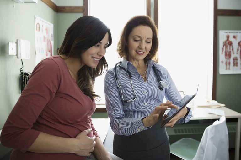 Doctor and pregnant woman looking at digital tablet