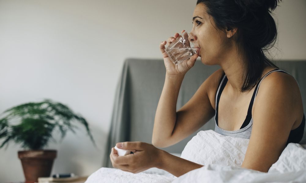 woman drinking water in bed