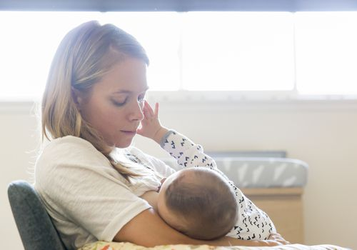 Millennial mother breastfeeds baby in a nursery