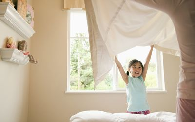 Little girl holding up a bed sheet with her mother.